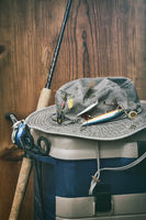Hat with fishing equipment against wood wall