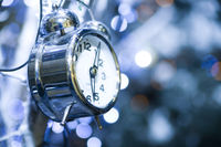metal clock on a holiday background with sparkles