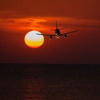 Passenger plane flying at a low altitude at sunset and the sun background