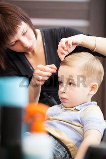 Hairdresser finishing boys haircut with hair setting