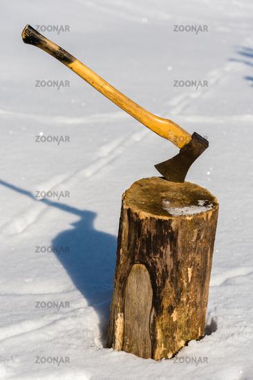 Ax stuck in wood log snow winter