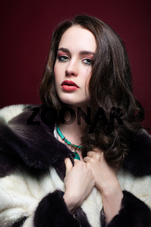Young beautiful woman in fur coat and with green pistachio colour eyes on red marsala background