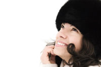attractive smiling girl in warm fur hat on a white