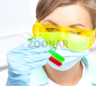 doctor in a mask examines test tubes