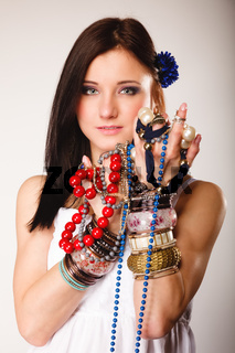 summer girl with plenty of jewellery, beads in hands
