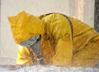 man in a yellow chemical protection suit running in the rain