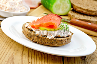 Sandwich with cream and salmon in oval plate on board