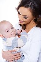 Loving mother cradling her happy baby son