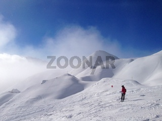 A skier on the piste in front of beautiful mountains