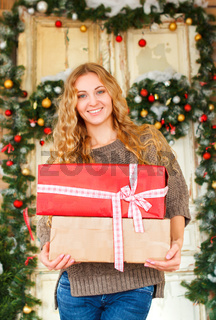 Young happy blond woman holding Christmas presents