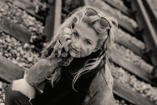 Junge Frau in Jeansjacke sitzt auf Gleis