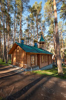 Wooden chapel in pine forest in Chemal