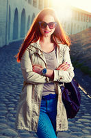 Street fashion portrait of young foxy-haired woman in a jeans and violet sunglasses with a leather handbag against the setting sun. Cold season. Pink lips. Warm sunset colors.