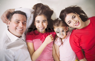 Happy young family with kids lying on a floor at home