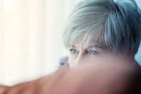 Portrait of a Senior, hiding behind a pillow, attentive look.