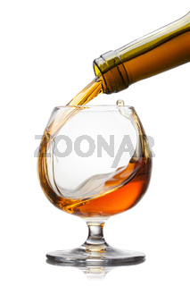 Cognac pouring into glass with splash isolated on white backgrou