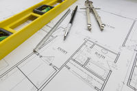 Construction Level, Pencil, Ruler and Compass Resting on House Plans