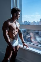 Image of bodybuilder posing standing at window