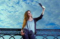 Young beautyful women use phablet for selfie photography in bright day against cloudy sky