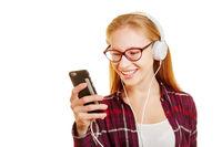 Frau mit Smartphone und Kopfhörer hört Musik