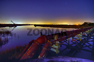 industrial pipes and ocean harbor landscape at night