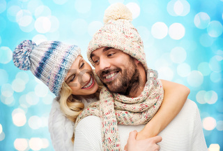 happy couple in winter clothes hugging over lights