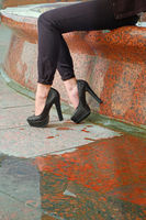 Closeup of young woman legs on red granite cobblestone street with puddle and reflection. Beautiful female legs in fashion shoes with high heels on granite pavement