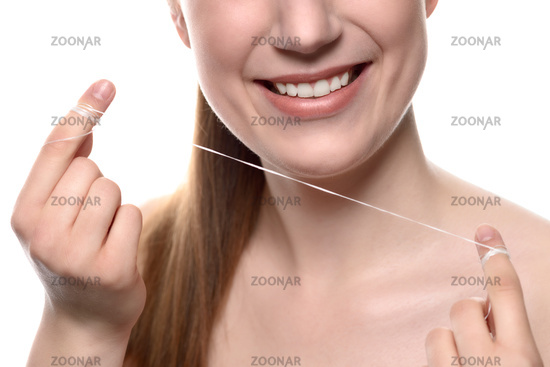 Woman with healthy white teeth with dental floss