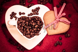 Coffee beans in heart shaped cup and dessert on red
