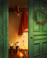 Open rustic door with Santa hat and outfit hanging