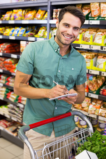 Portrait of smiling man writing on his notepad in aisle