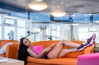 Nice brunette relaxing while lying on sofa in gym