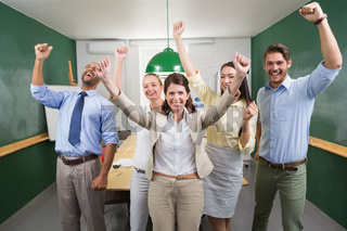 Excited business team cheering at camera
