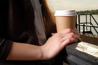Woman hold takeaway cup of coffee on fence closeup.