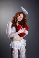 Innocent redhead girl dressed in angel costume