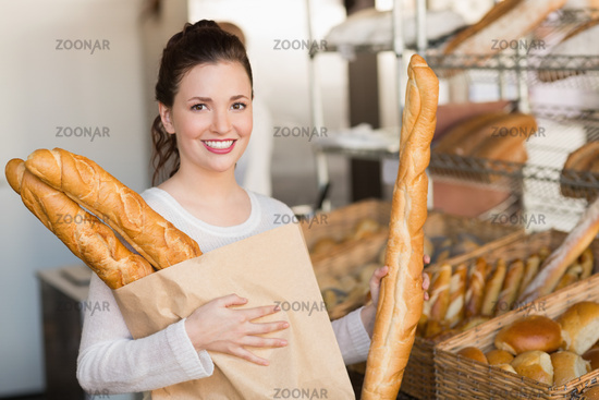 Pretty brunette holding bag of bread