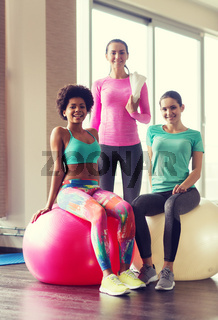 group of smiling women with exercise balls in gym