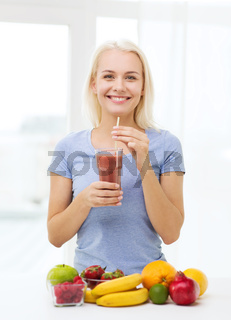 smiling woman drinking fruit shake at home