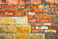 Dirty red brick wall half covered with tiles