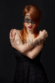 Red-haired beauty with lace mask on eyes