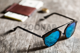 Stylish sunglasses with blue tinted mirror on textured wooden background