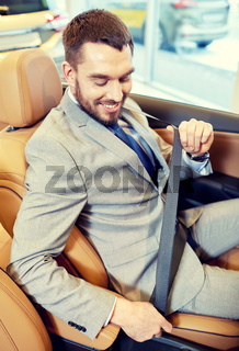 happy man sitting in car at auto show or salon