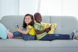 Smiling girl and boy using mobile phones
