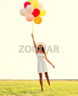 smiling young woman in sunglasses with balloons