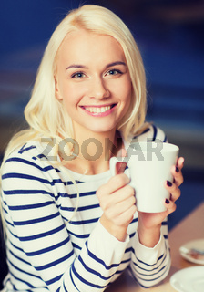 happy young woman drinking tea or coffee