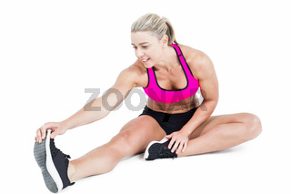 Female athlete sitting and stretching
