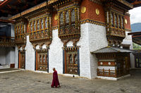 Buddhistischer Mönch durchschreitet den Innenhof der Klosterfestung Punakha Dzong