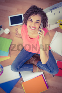 Smiling young creative businesswoman on the phone