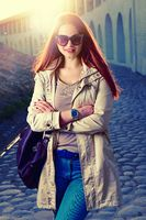 Funny stylish smiling beautiful young redhair woman in hipster clothes standing in the street with fashionable handbag,street fashion,red lips,funny sunglasses
