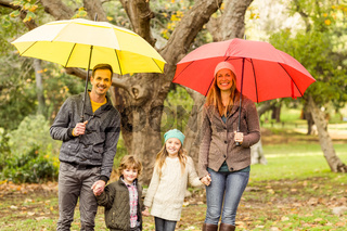 Smiling young family under umbrella